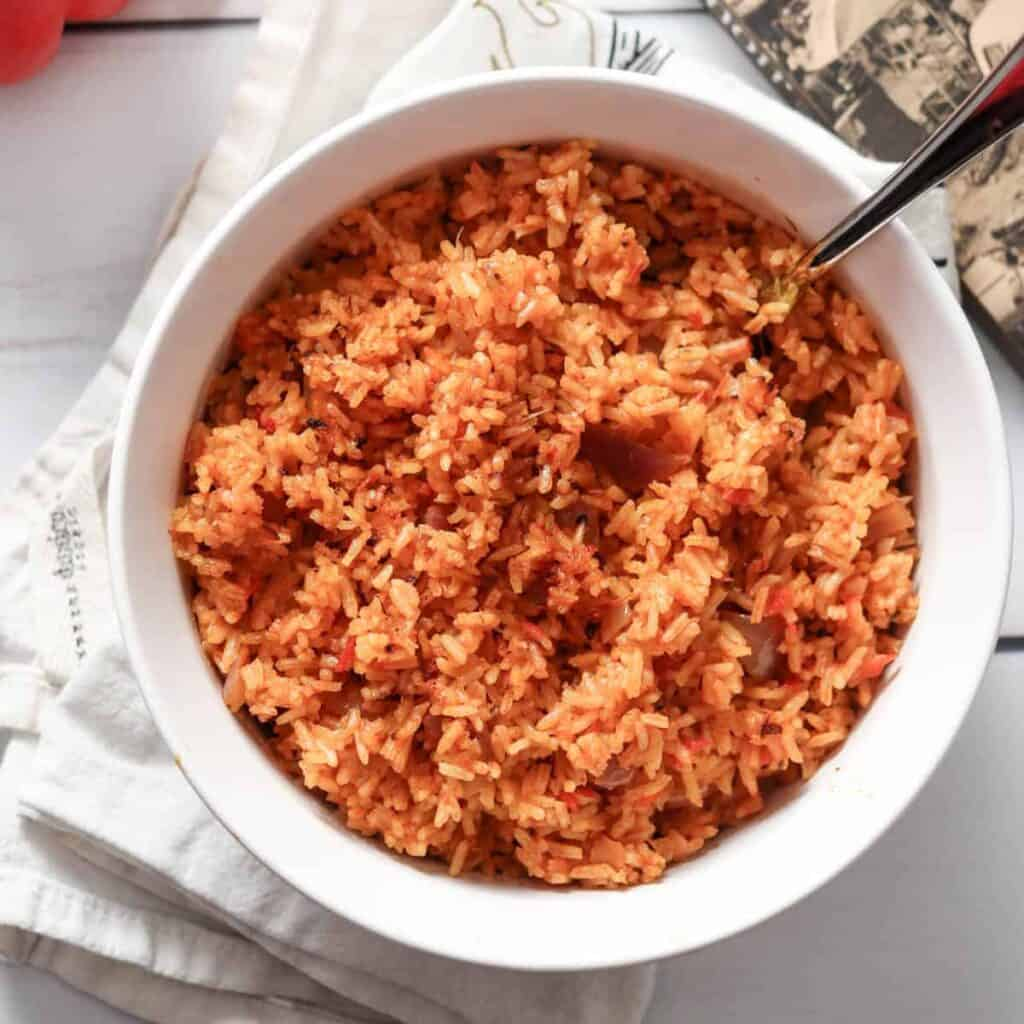 Bowl of Nigerian jollof rice with a spoon in it