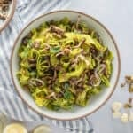 Close up of bowl of pasta with garnishes on the side