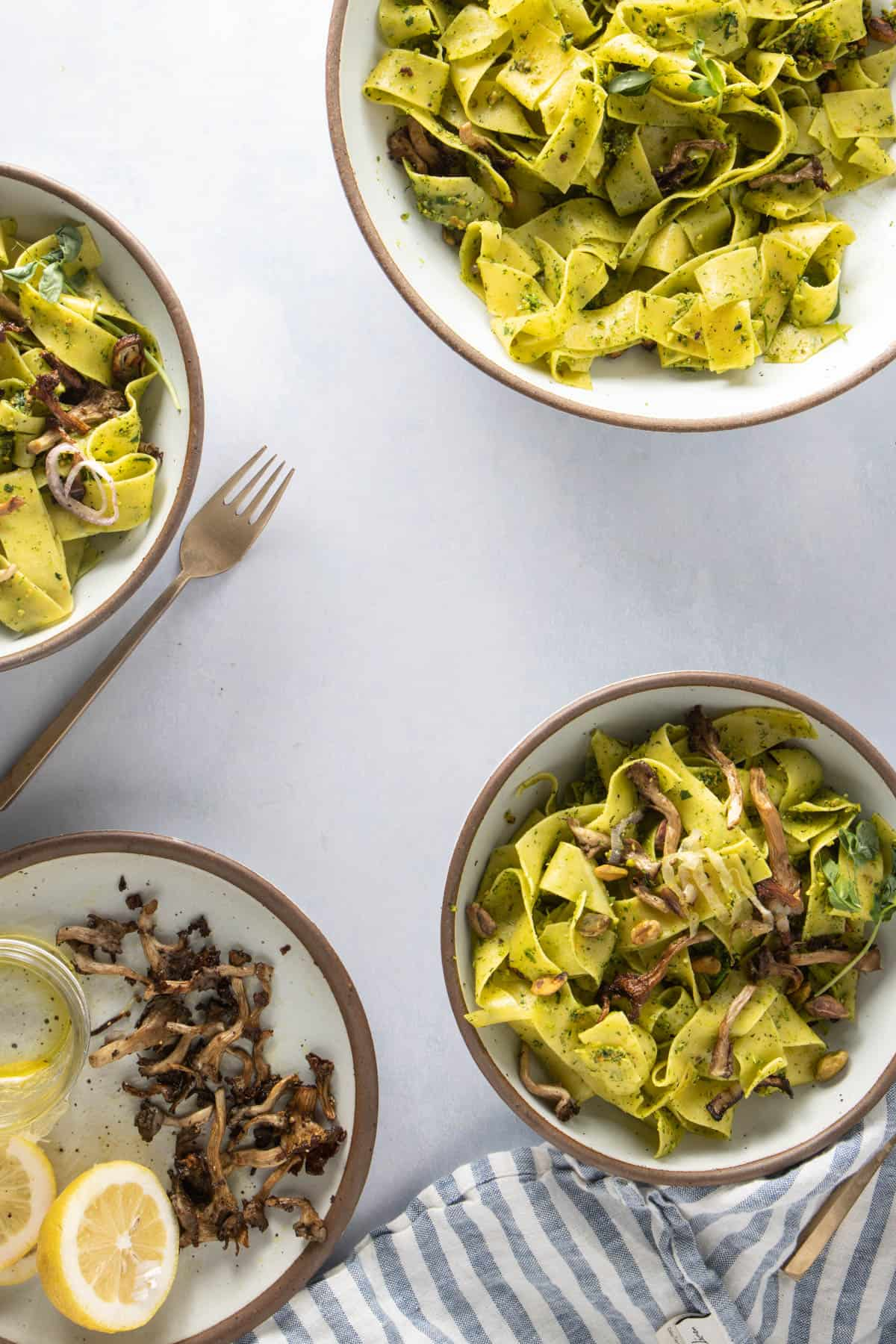 Three bowls of finished spring pasta, some garnishes on the side