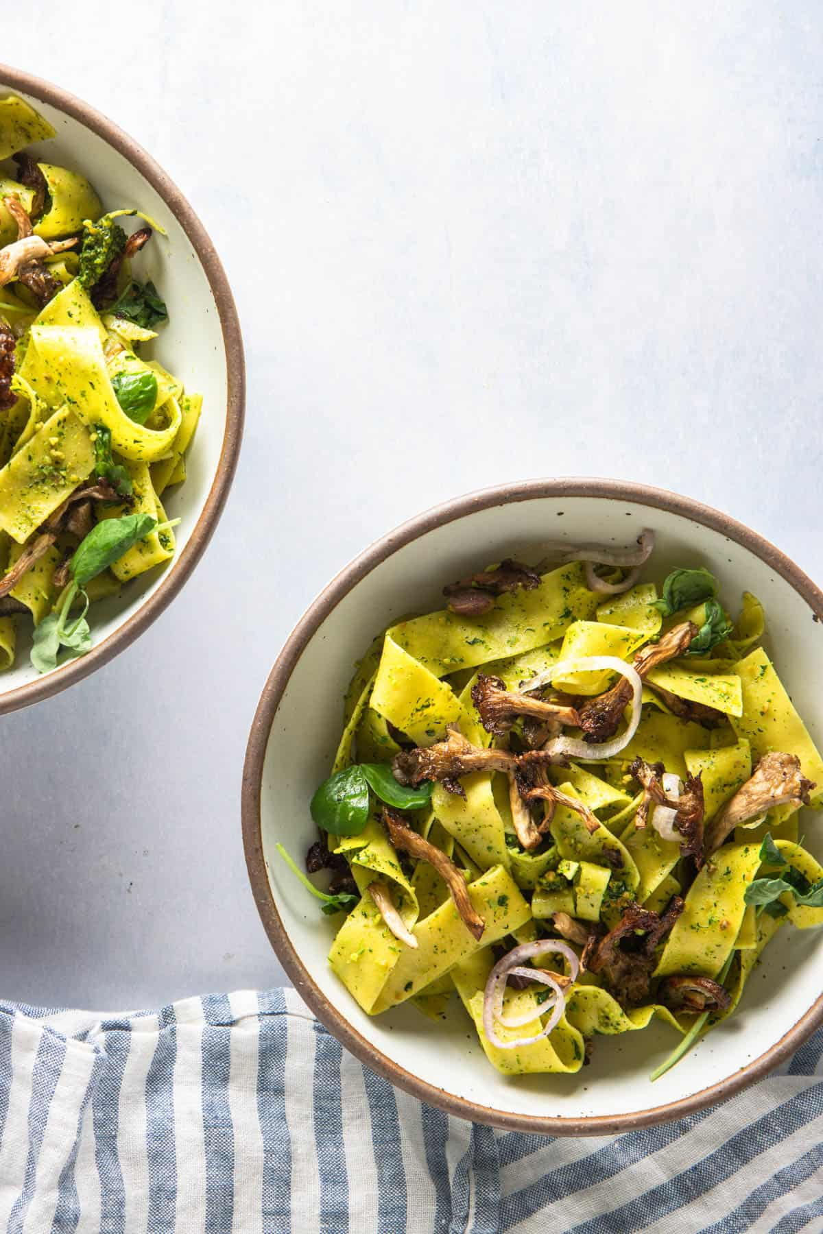 Two bowls of pea shoot pesto pasta with oyster mushrooms