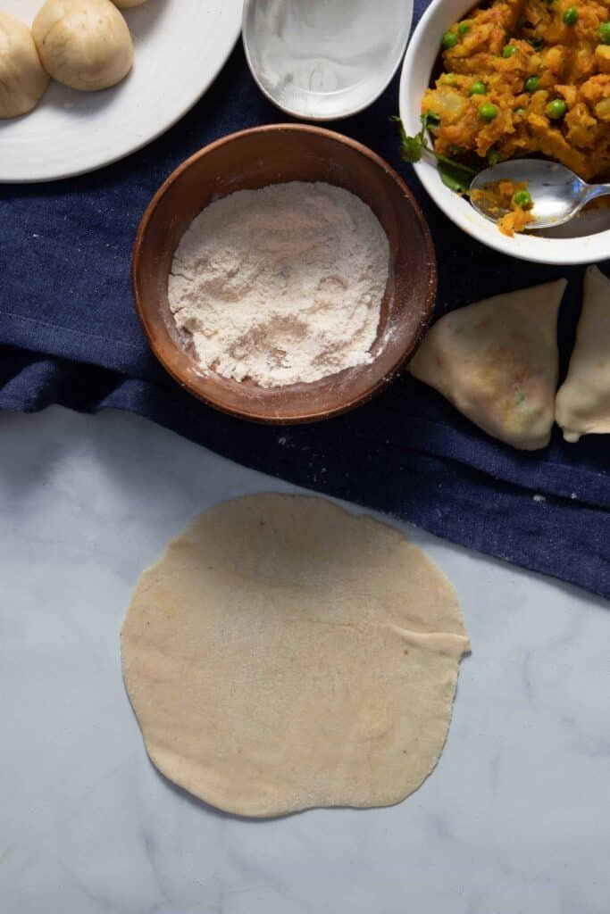 Then, roll the dough into a flat circle, about 1/2 cm thick like a tortilla or chapati