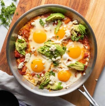 Delicious, Moroccan shakshuka with perfect runny yolk, garnished with parsley, avocado, and cheese