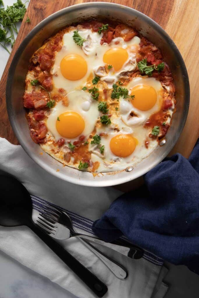 Shakshuka eggs in the skillet before adding all the other additional garnishes (except parsley)