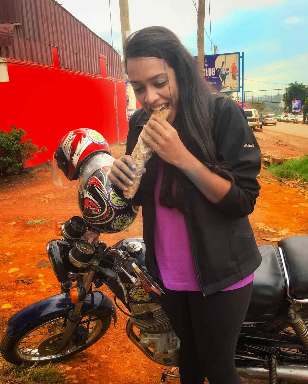 Shruthi eating a wrap in Uganda