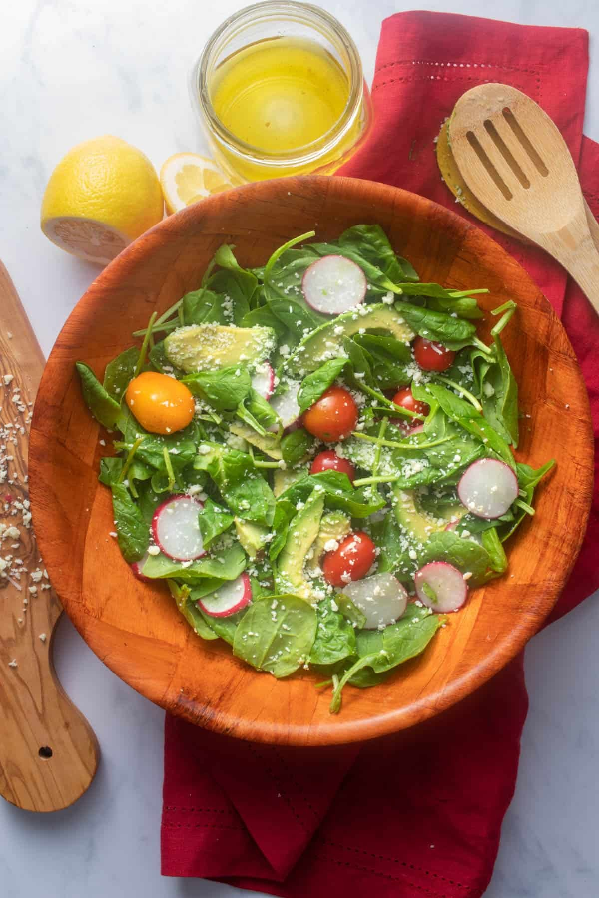 Assembled salad bowl with vinaigrette in the background