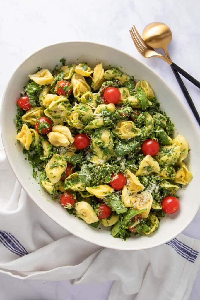 Serving platter with spinach tortellini salad, showing cherry tomatoes and drizzle of vinaigrette
