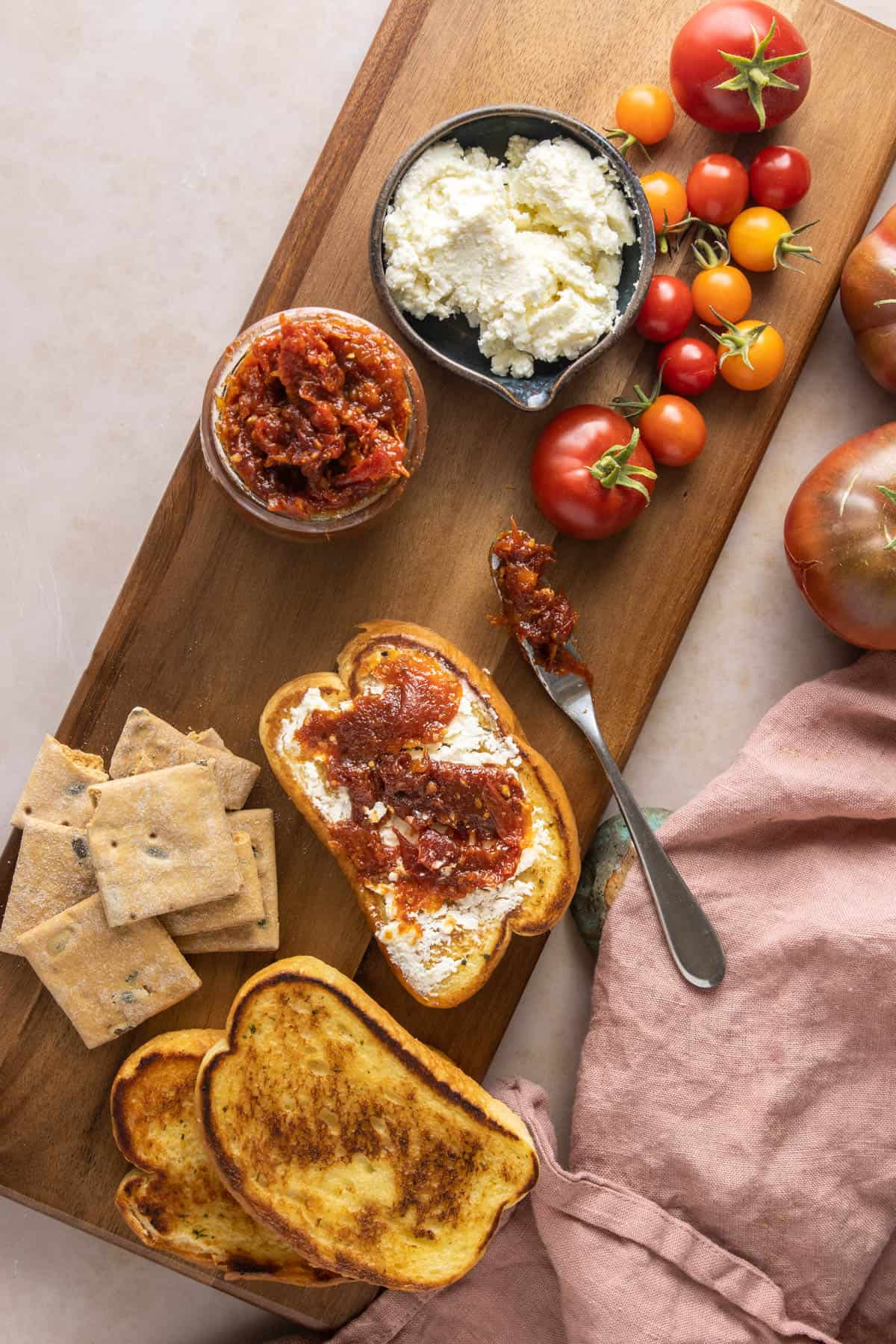 Overhead shot of a platter with bread, tomato jam, and whipped feta