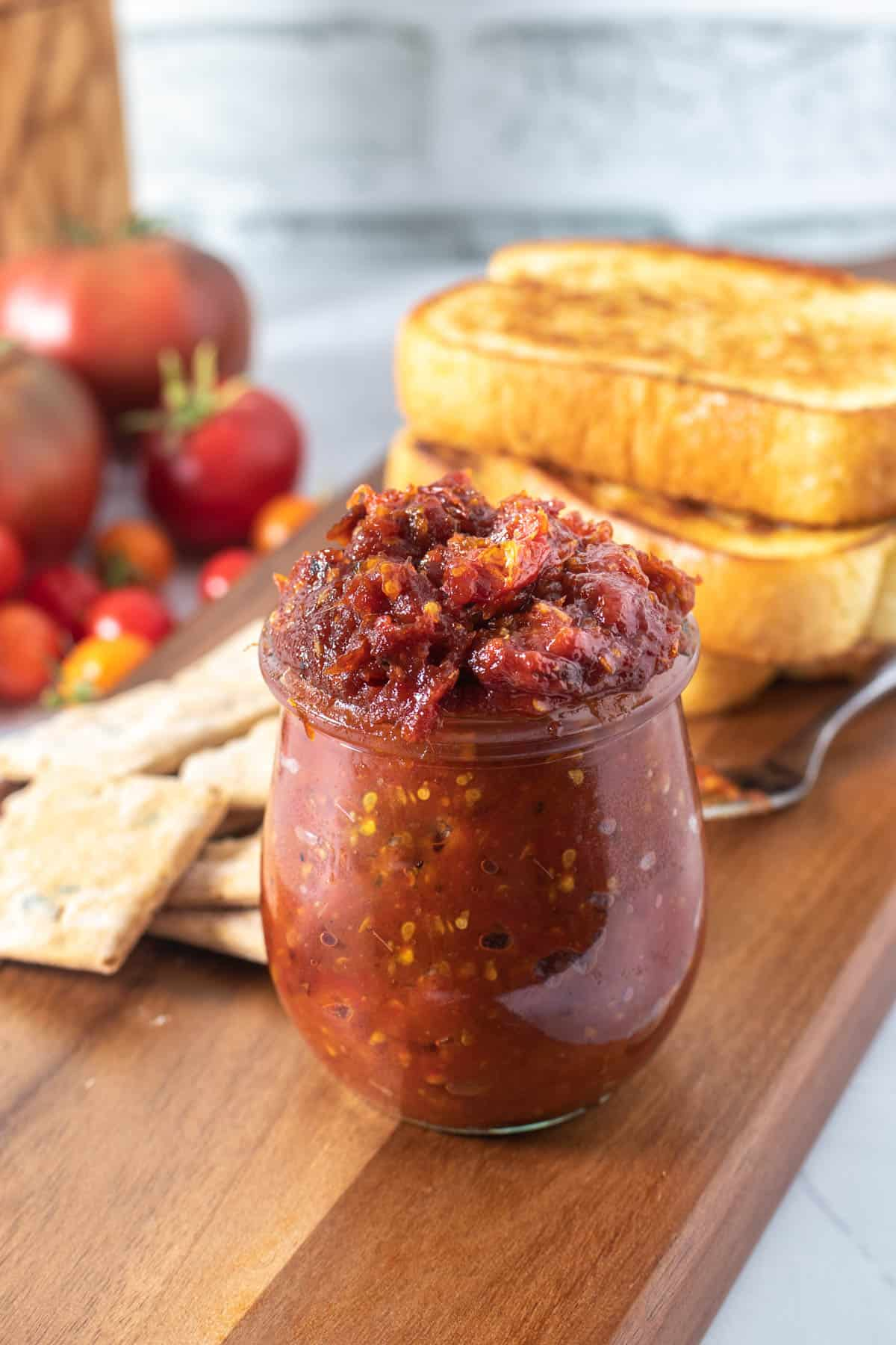 Close up of jar of tomato jam on wood platter with bread and tomatoes in background