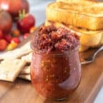 Close up of tomato jam in a jar on a wooden platter with accompaniments in the background