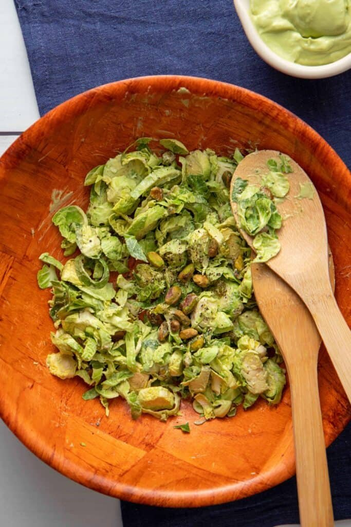 Delicious bowl of vegan Caesar salad with shaved Brussels sprouts and pistachios