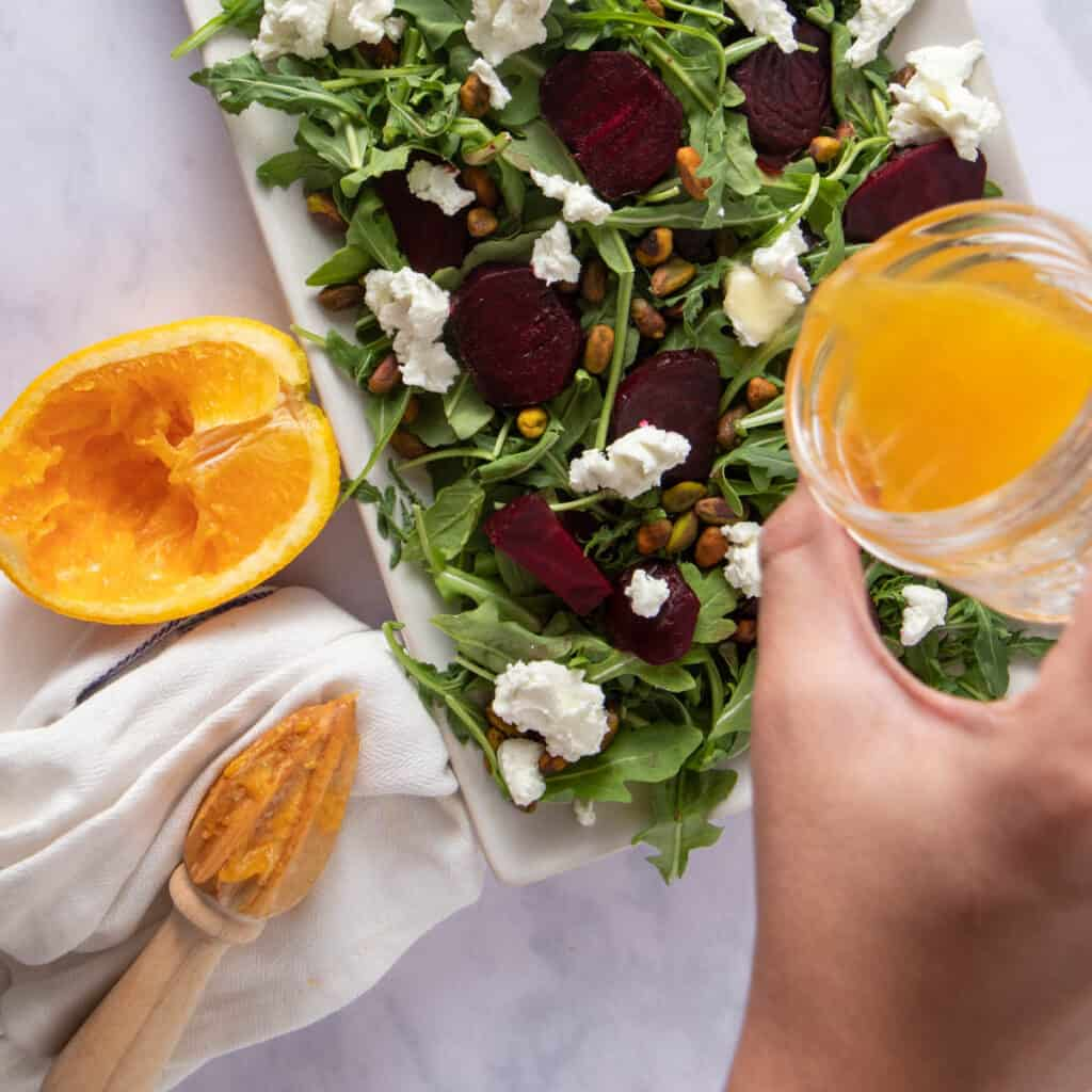 Pouring vinaigrette over salad