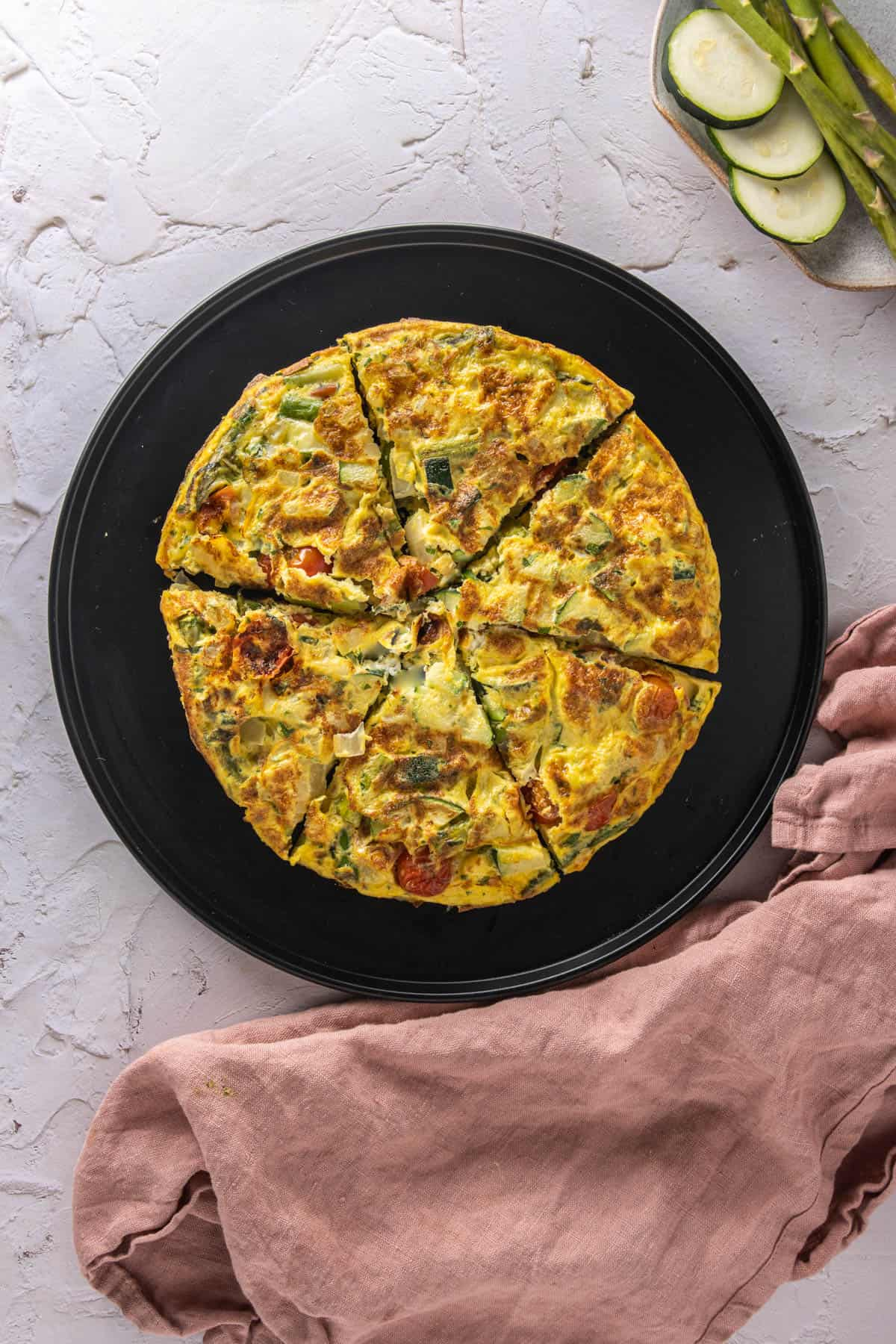 Frittata on a black serving platter with a pink napkin