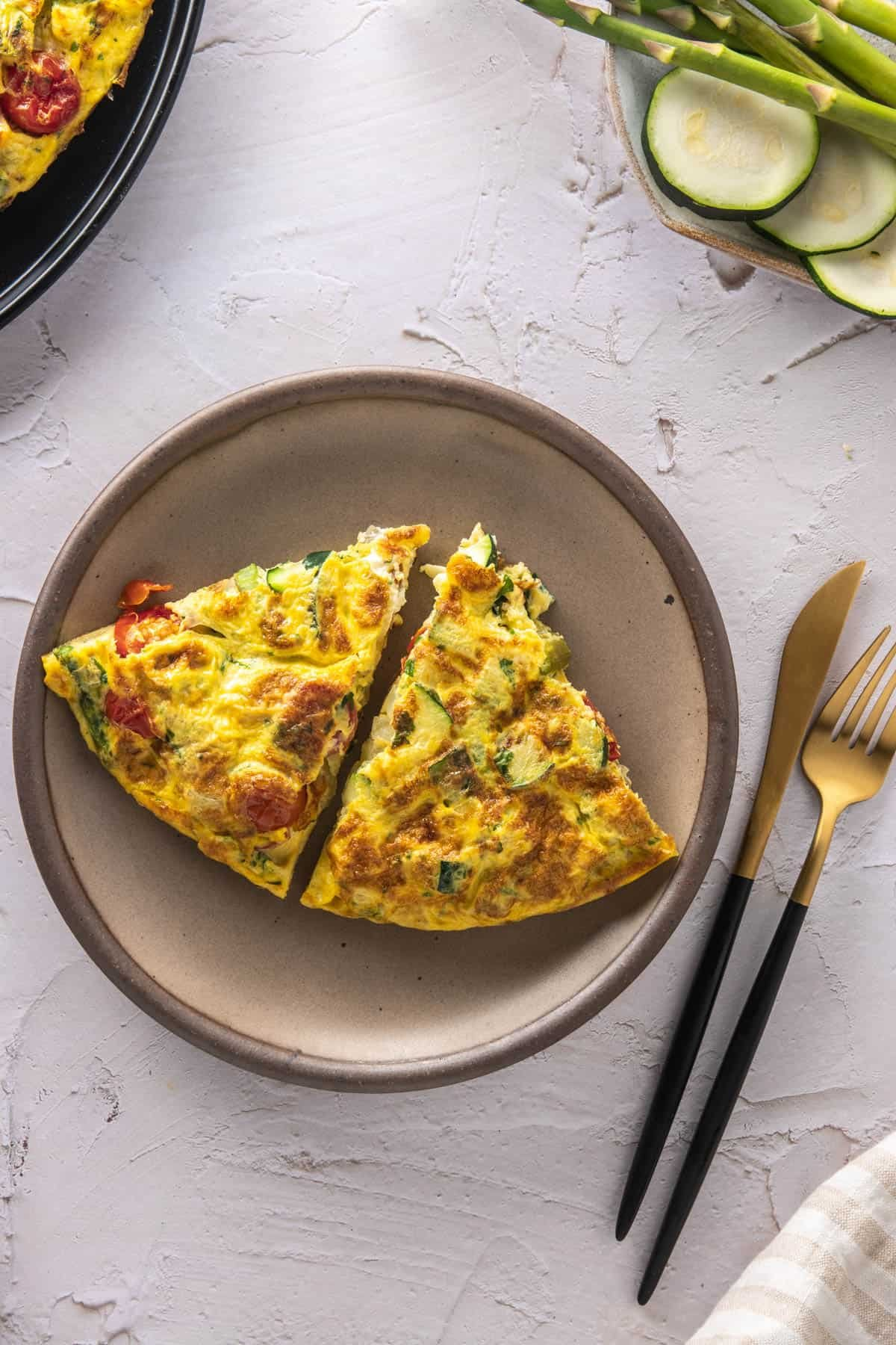 Plate with two slices of frittata and utensils next to it